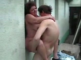 Granny with curly hair puts a dick in her mouth and cunt