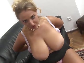 A hot milf with massive udders takes a big cock on the couch